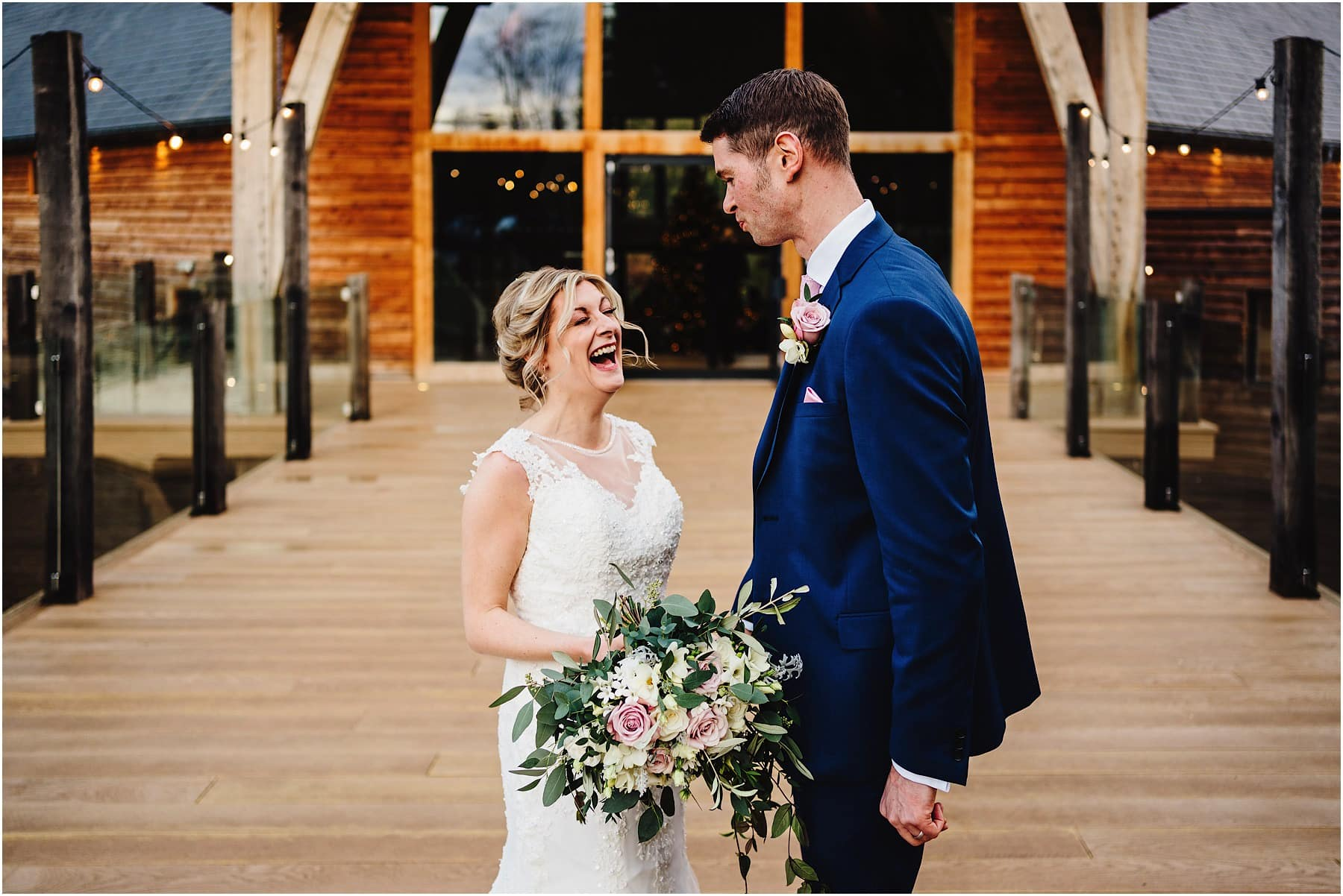 bride and groom laughing at mill barns