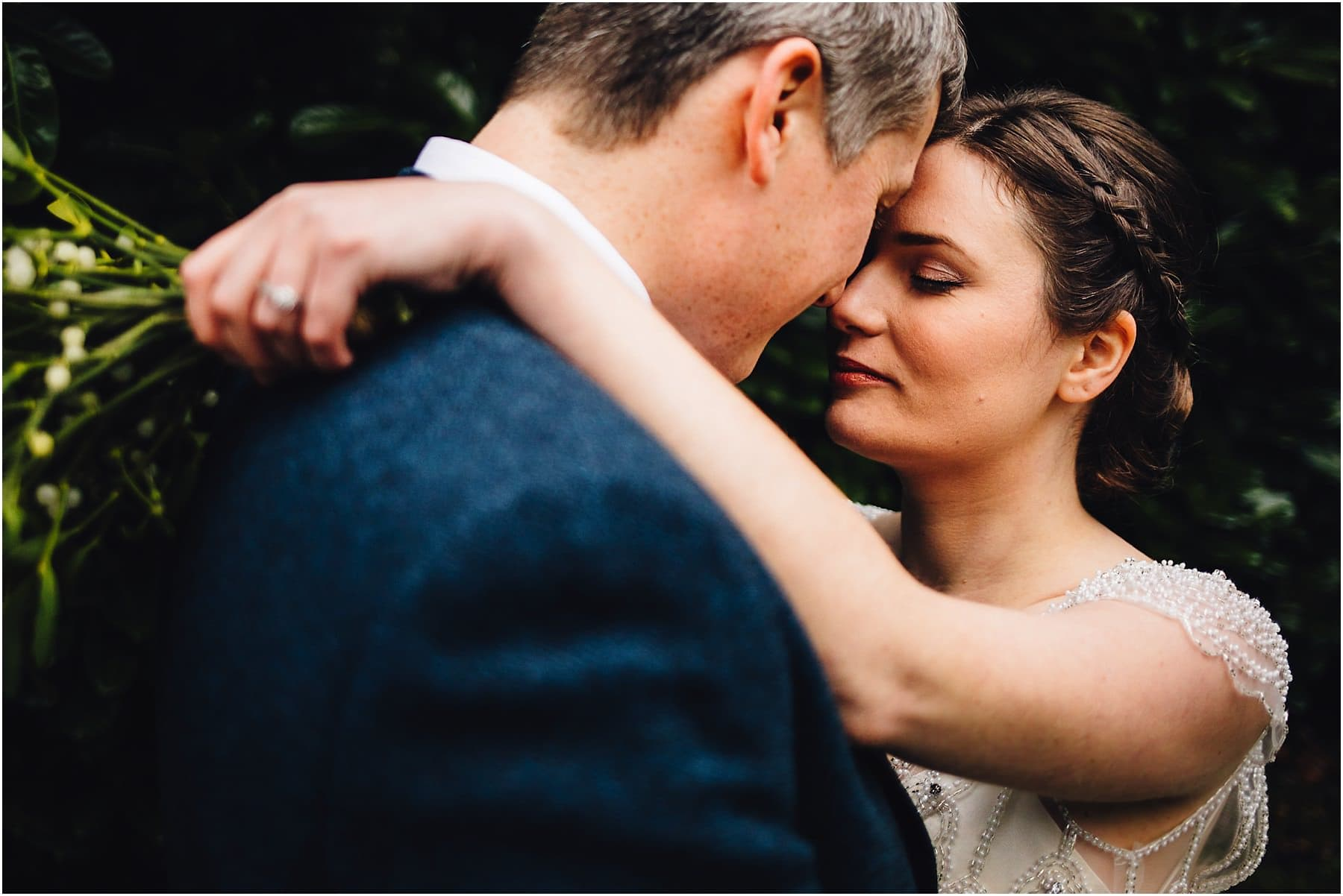 bride and groom touching heads with eye closed