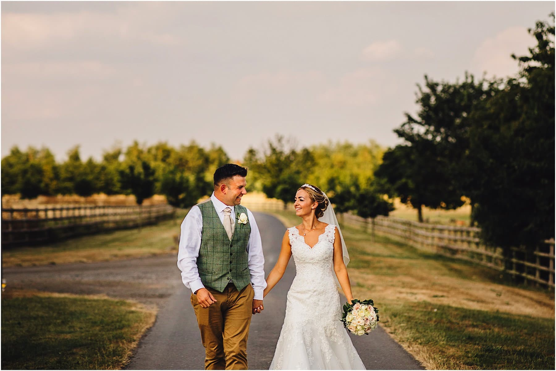bride & groom strolling up the drive at Mythe Barn