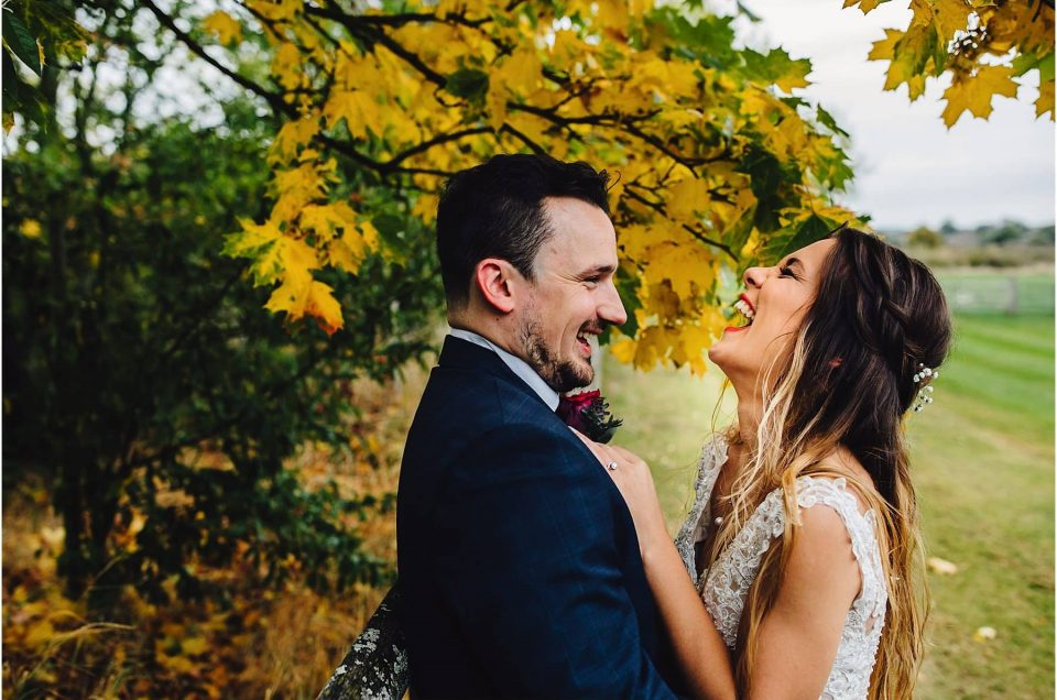 bride and groom laughing in the grounds of Mythe Barn Wedding Venue