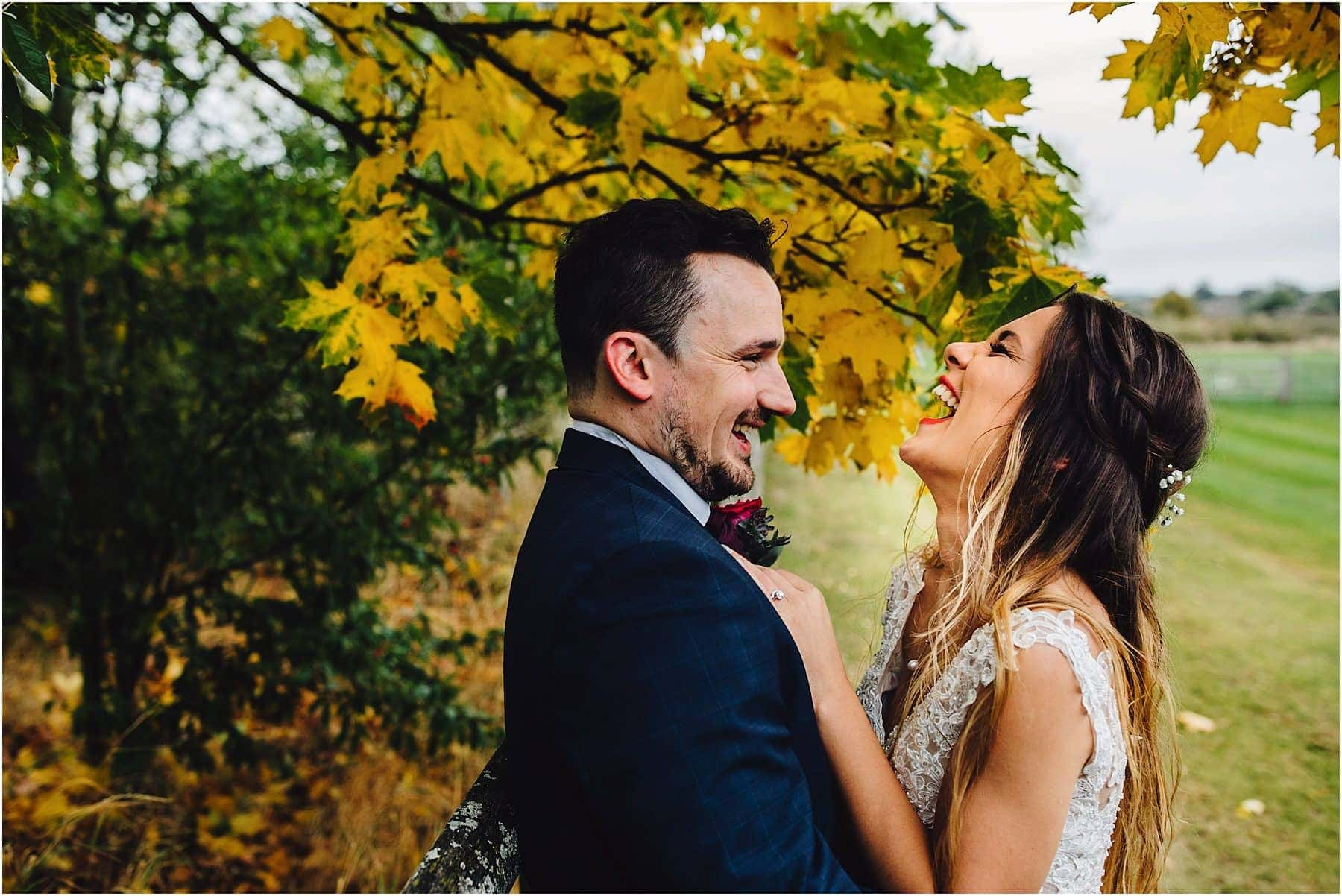 bride and groom laughing in the grounds of Mythe Barn