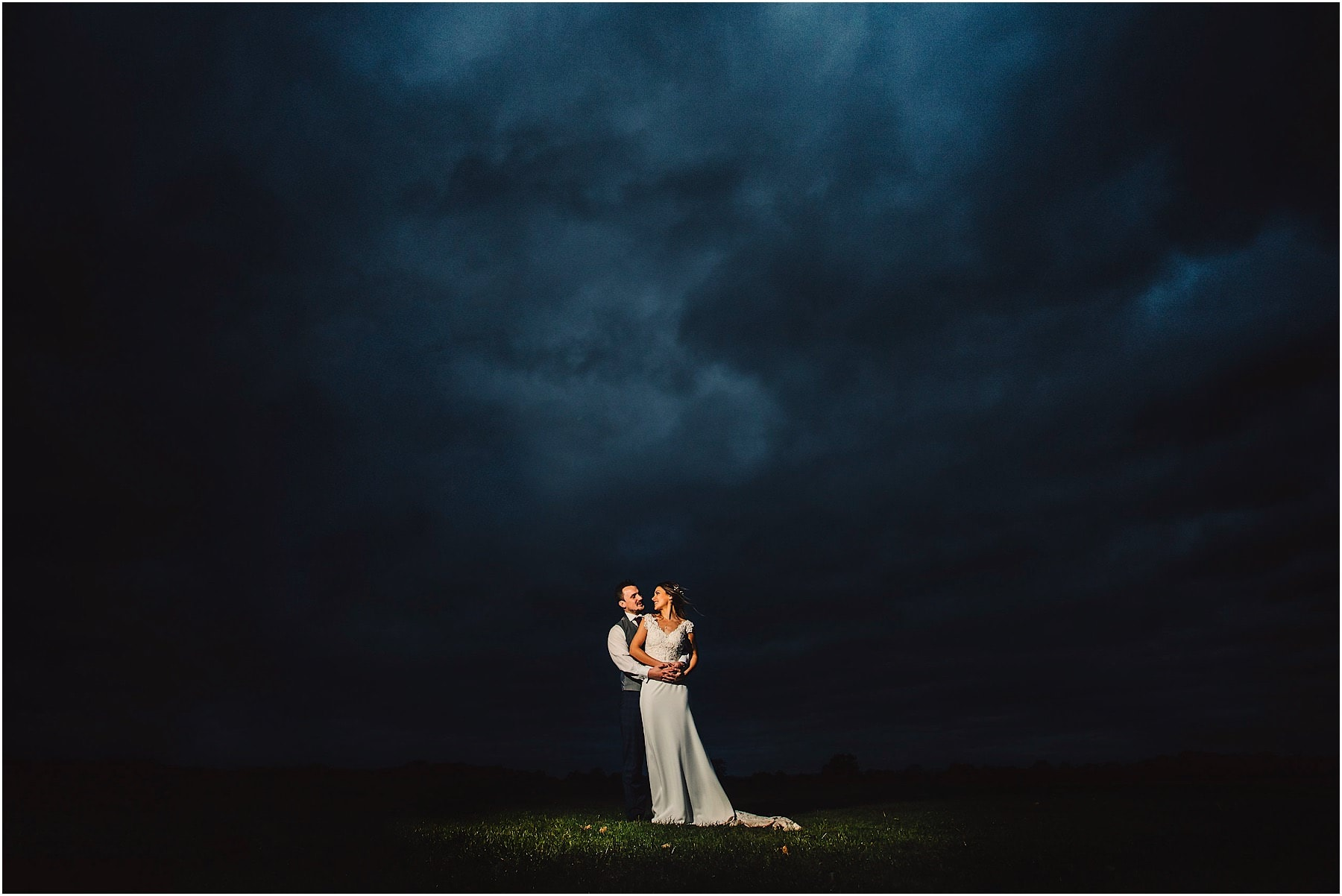 dramatic wedding portrait of bride & groom with a moody sky