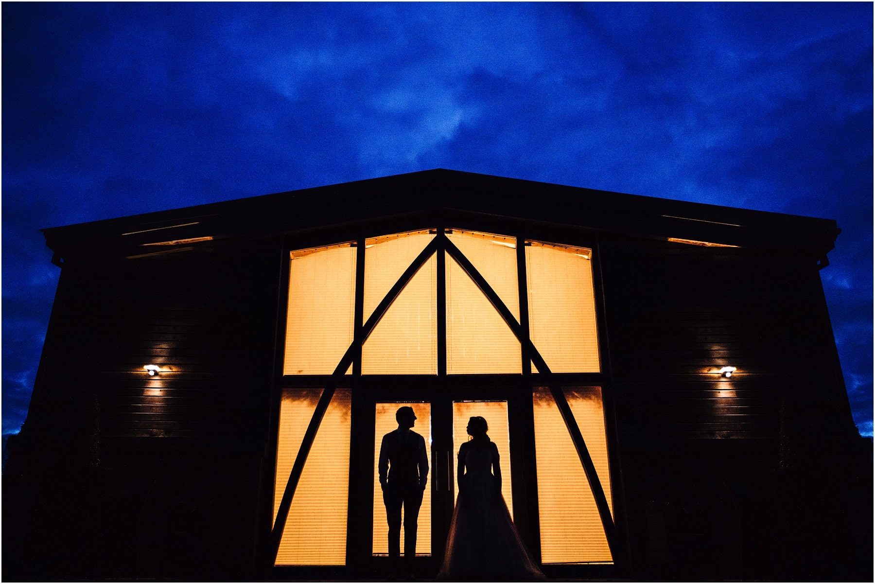 silhouette of a bride and groom against the barn at Mythe Farm