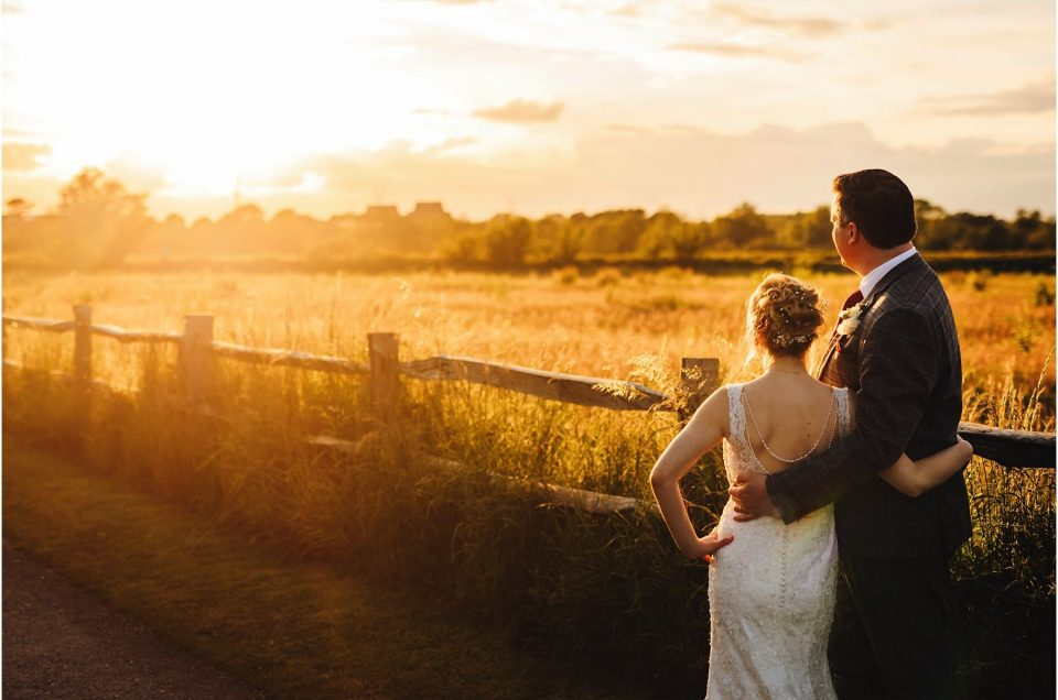 bride and groom looking off in to the sunset