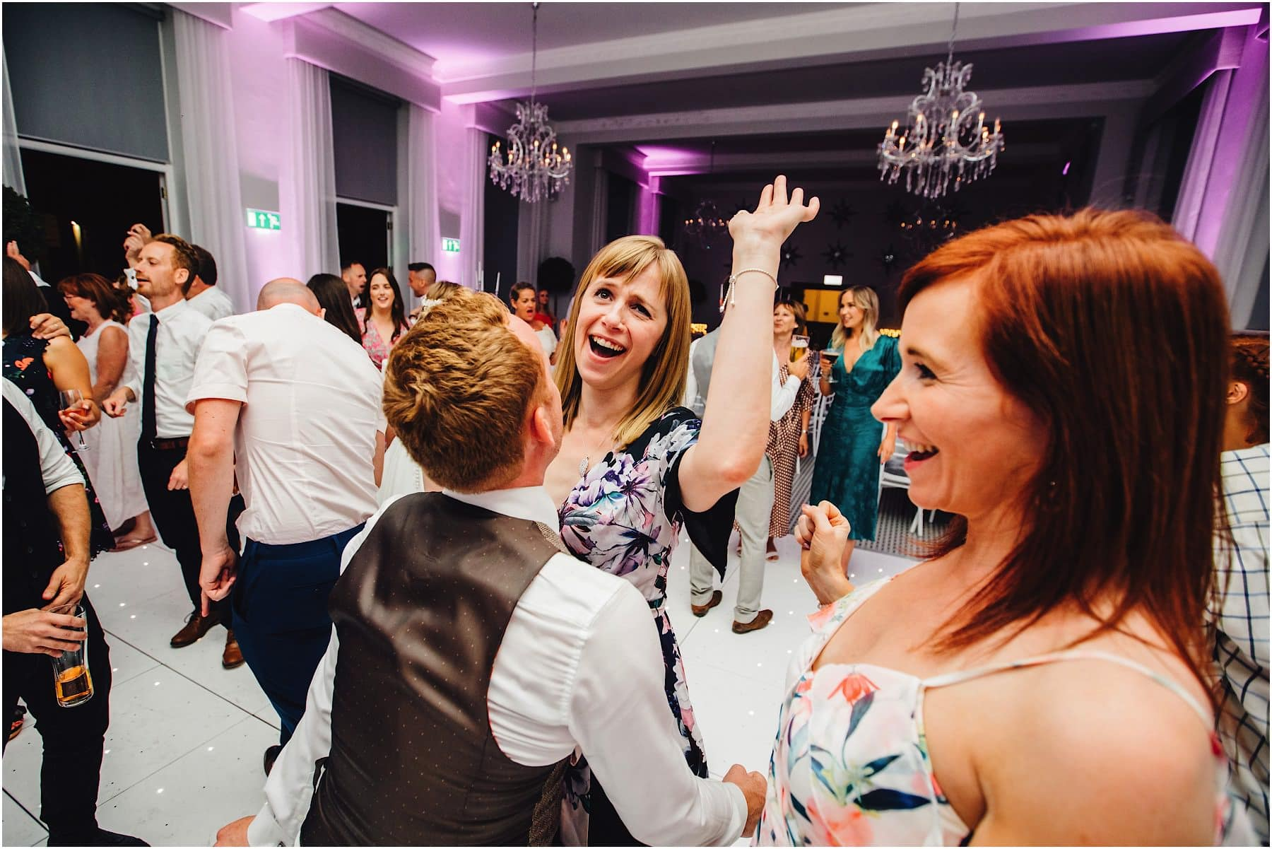 wedding guest dancing with arms in the air