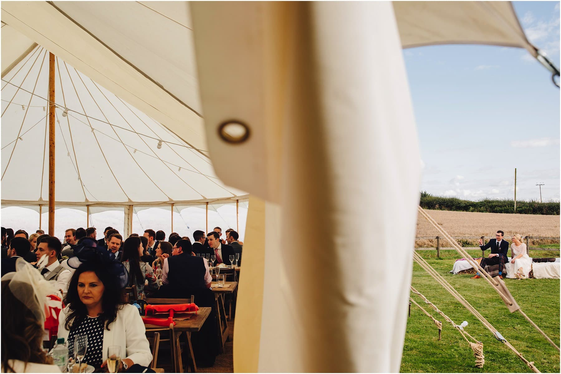 wedding guests in a marquee with bride and groom outside