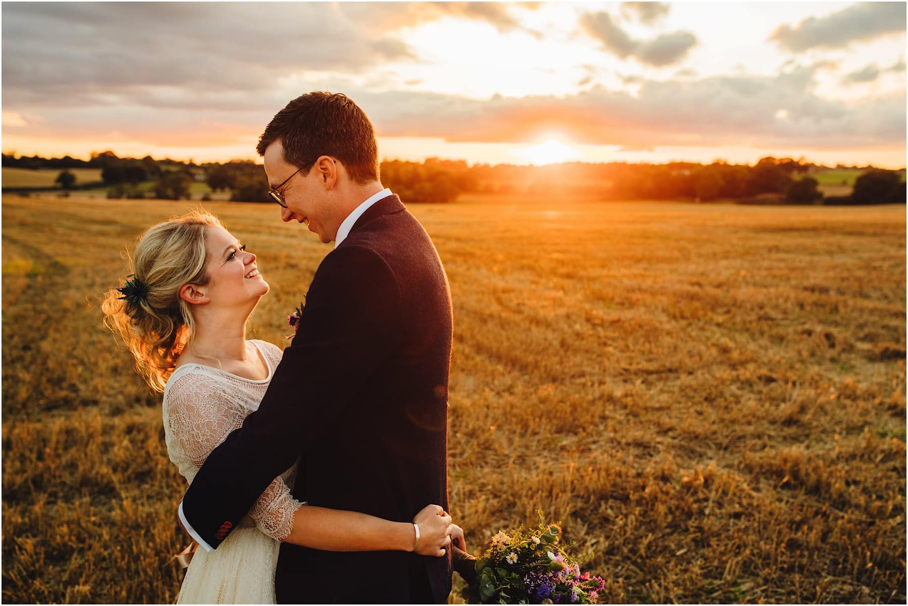 bride and groom hugging in a sunset