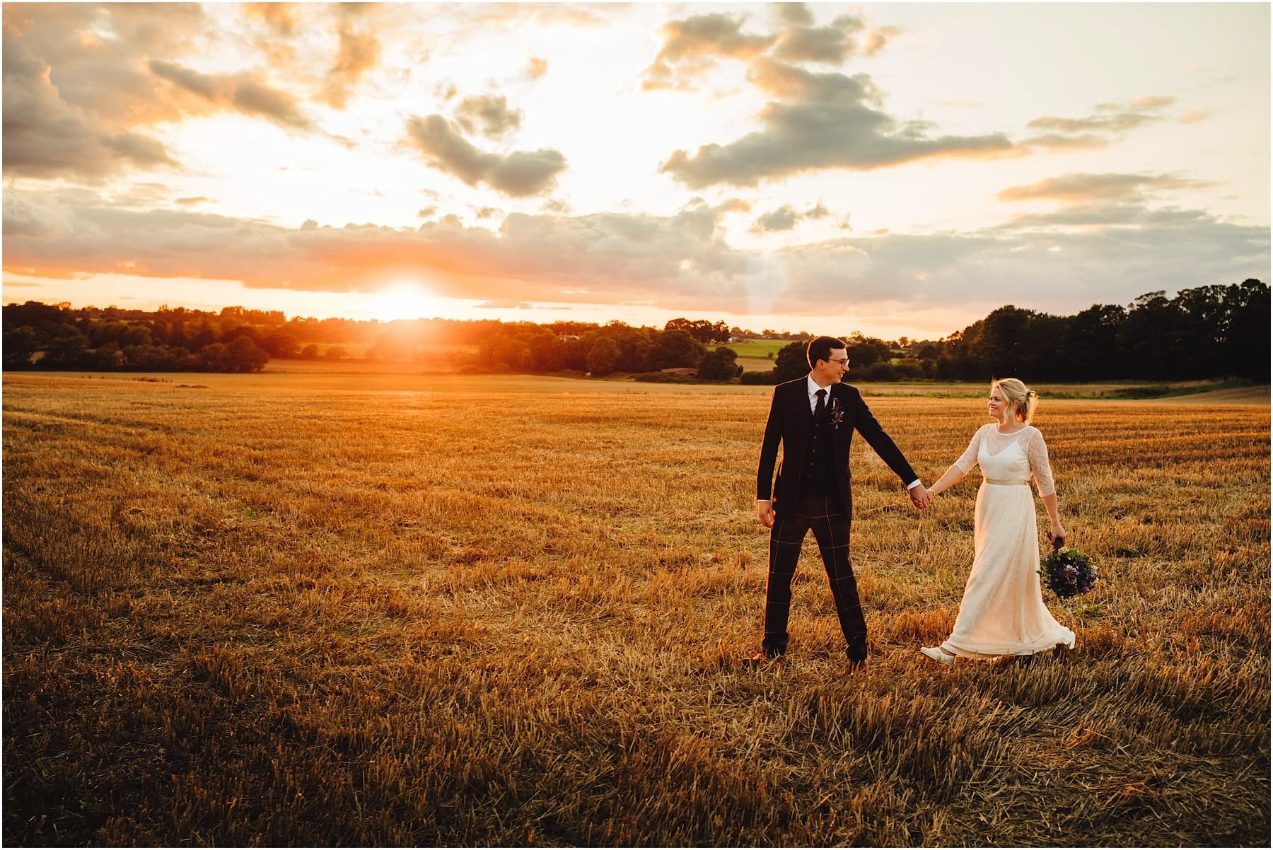 bride and groom walking across a field during sunset
