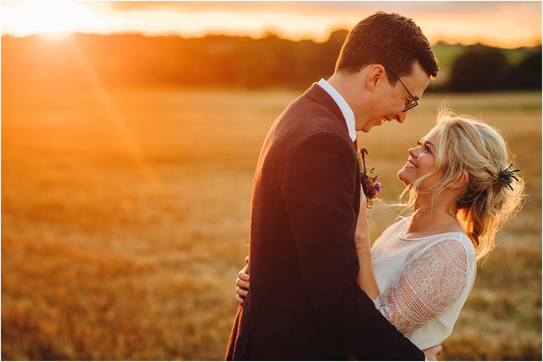bride and groom laughing in a sunset
