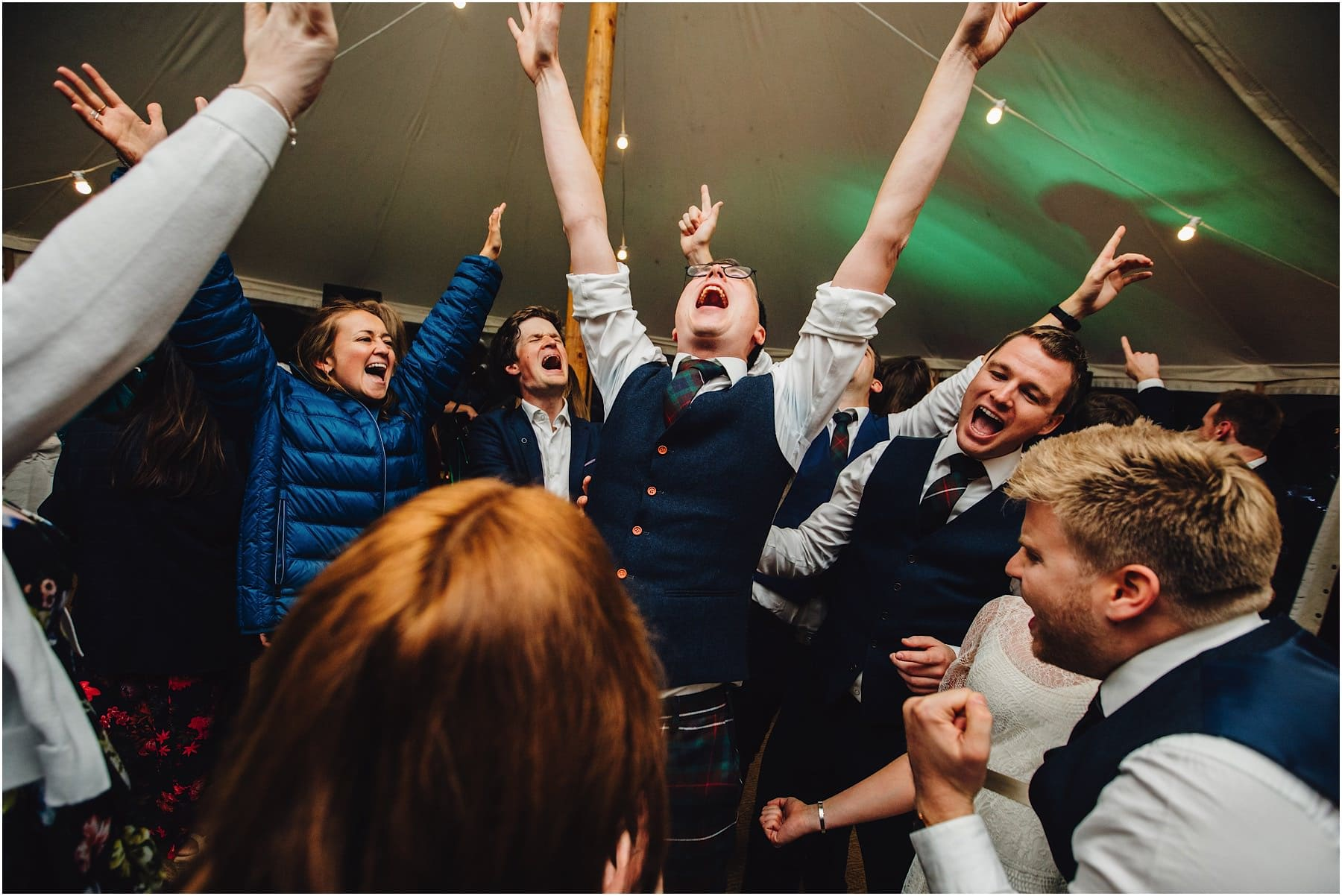 groom throwing his hands in the air
