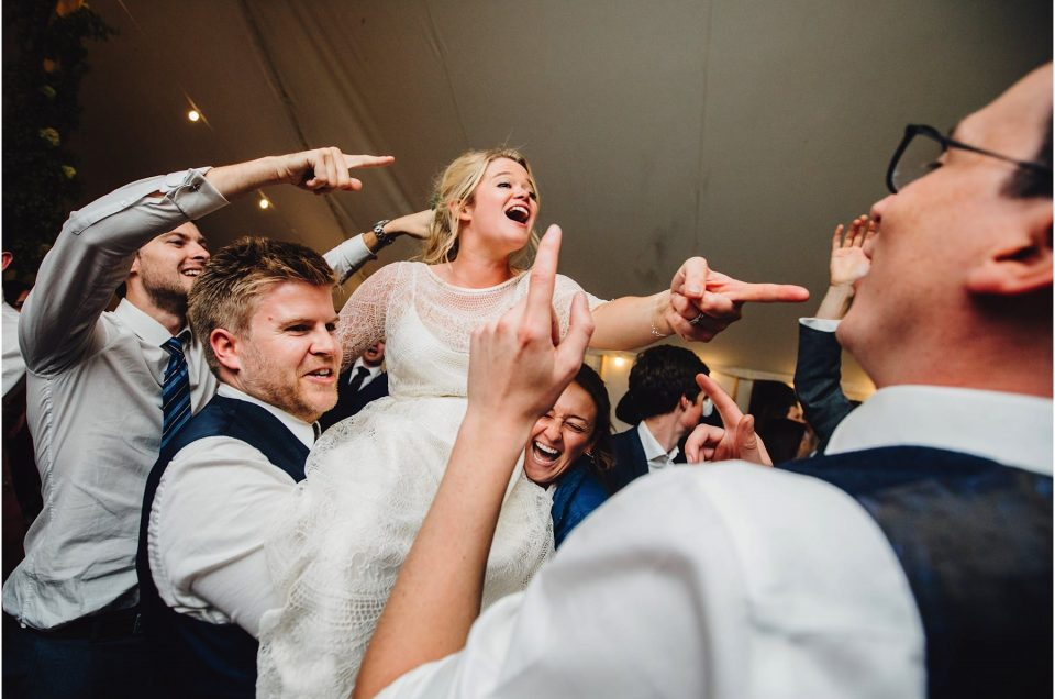 bride lifted on wedding guests shoulders