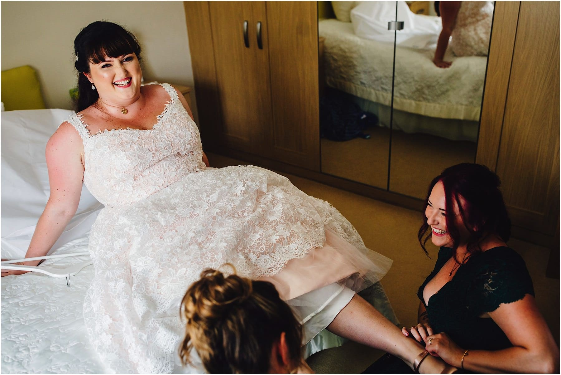 bride lying on the bed getting her shoes put on