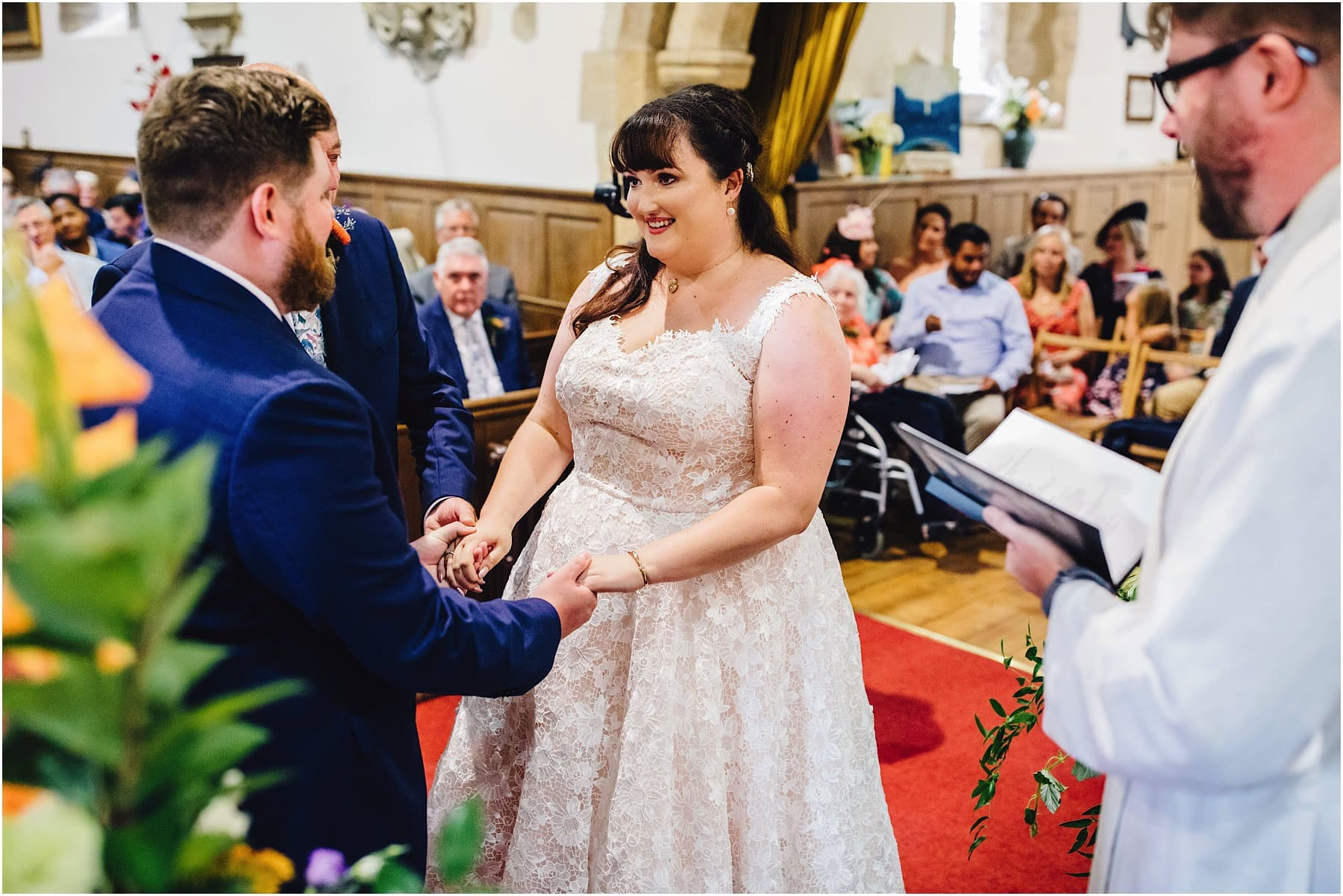 bride and groom holding hands at the end of the aisle