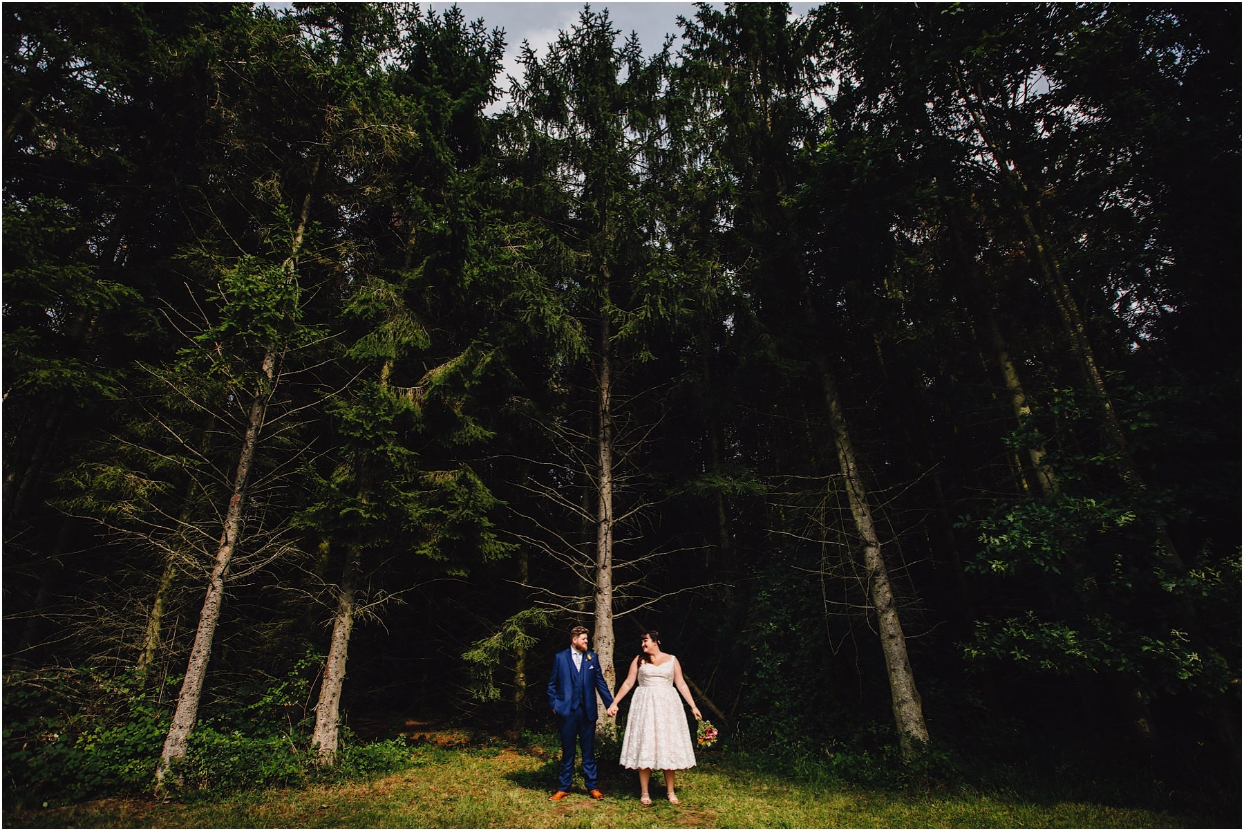 bride and groom standing infant of tall trees
