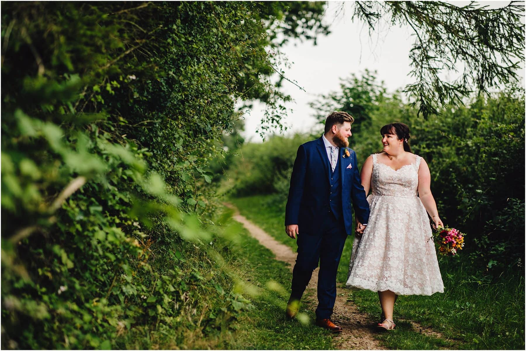 bride and groom strolling through the grounds of Lenches Lakes wedding venue