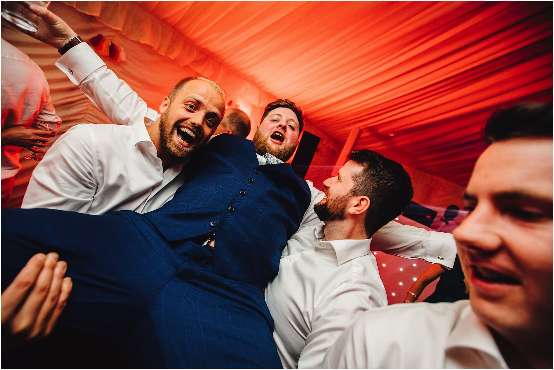 groom being picked up by groomsmen