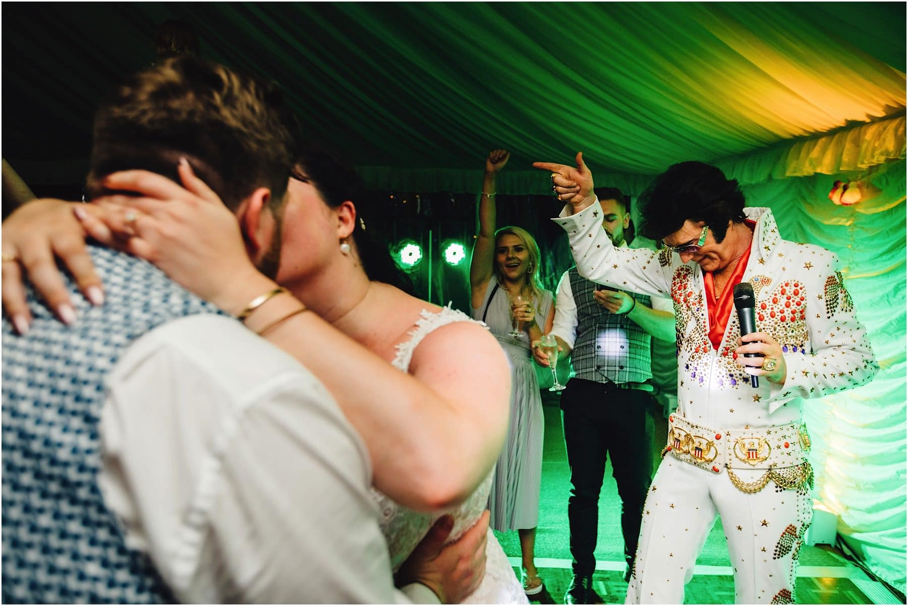 Elvis impersonator pointing at bride and groom