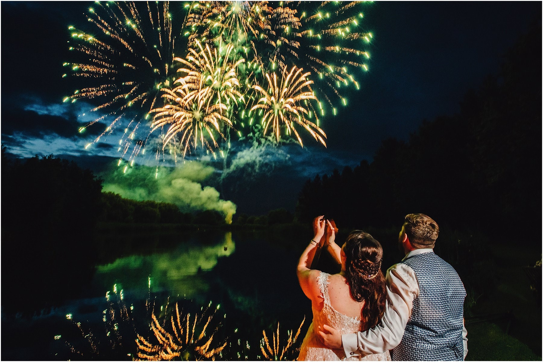 Bride and groom watching fireworks exploding over Lenches Lakes