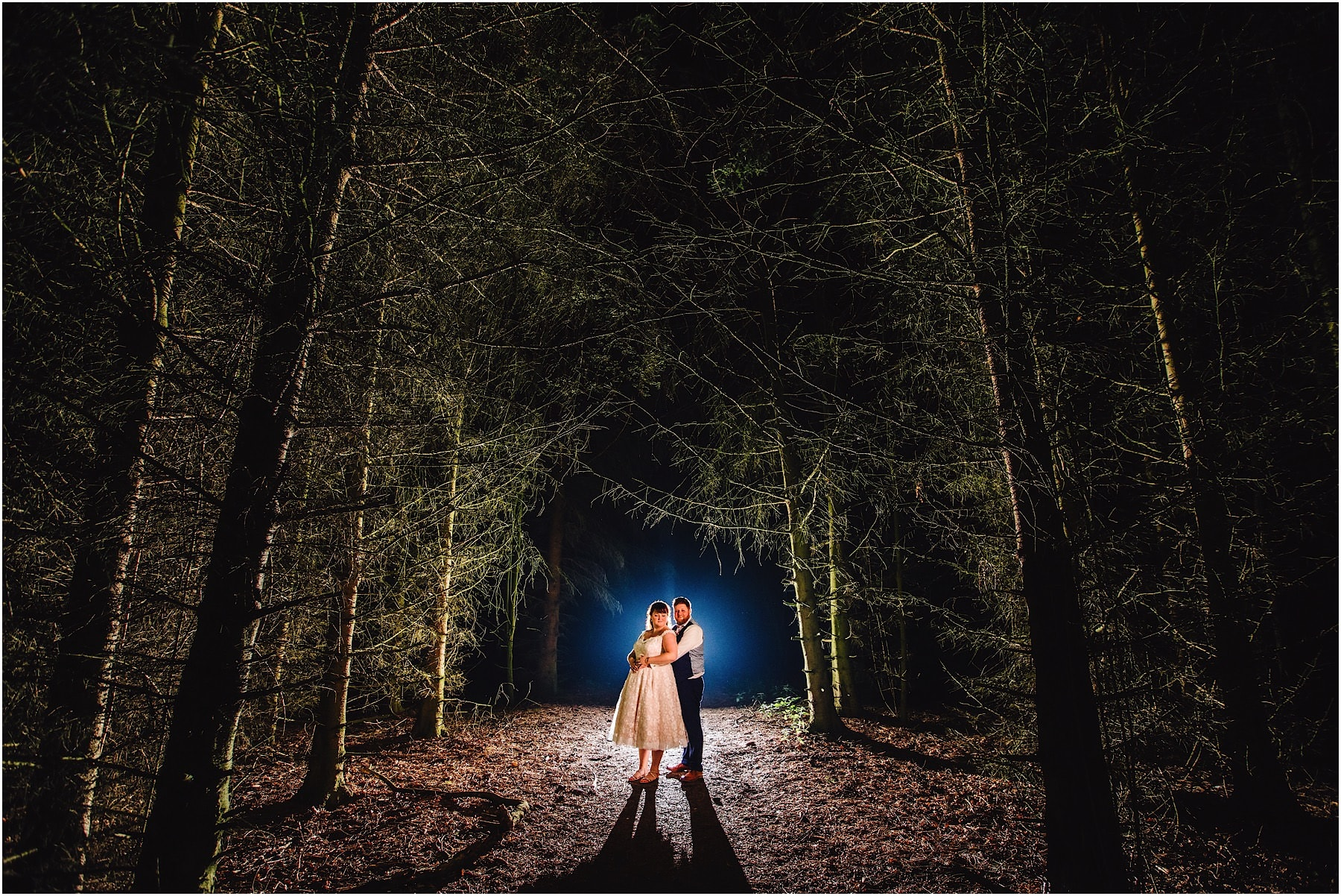 Bride and groom in the trees at night