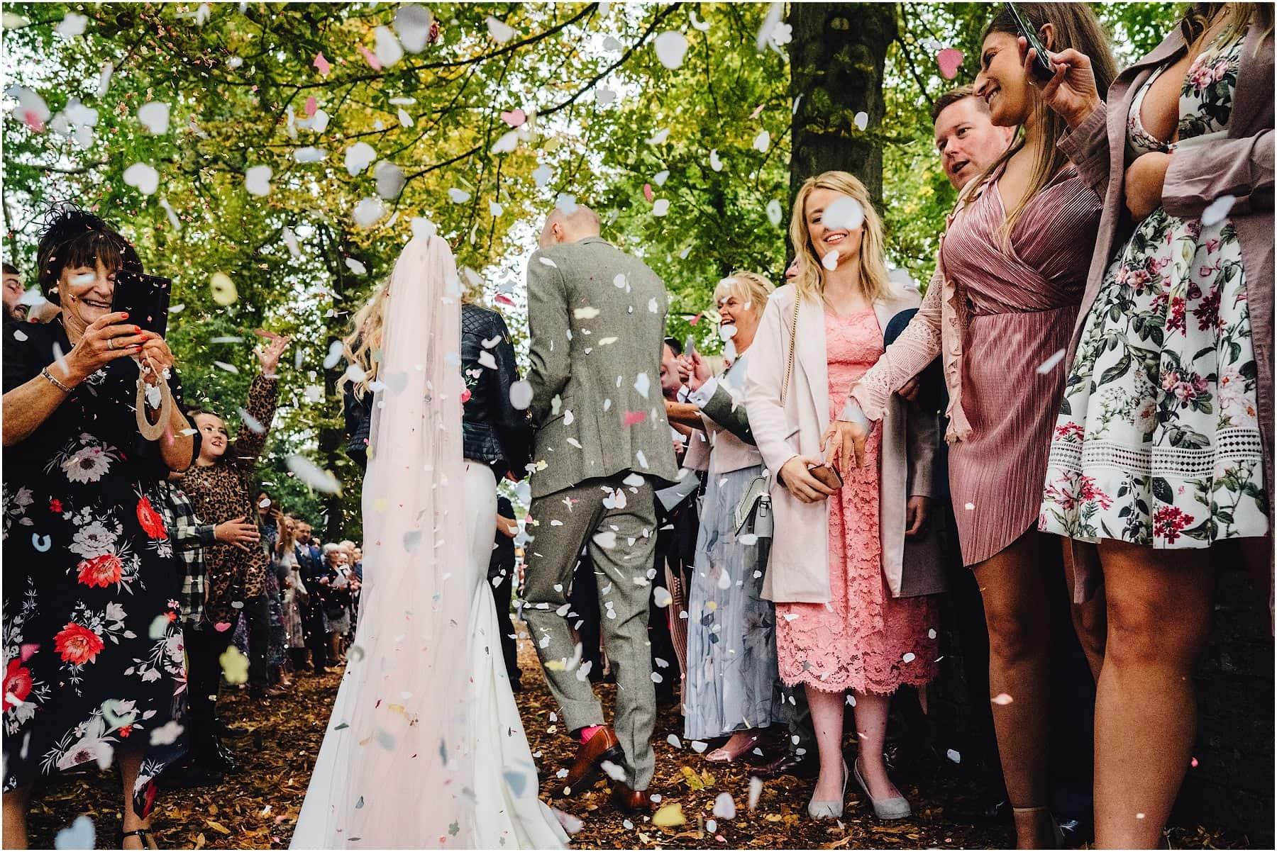 rear photo of bride and groom in a confetti tunnel
