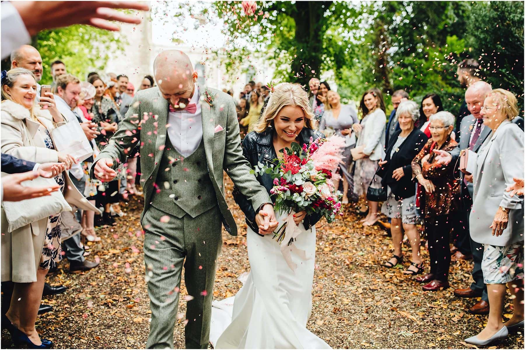 bride and groom having confetti thrown on them