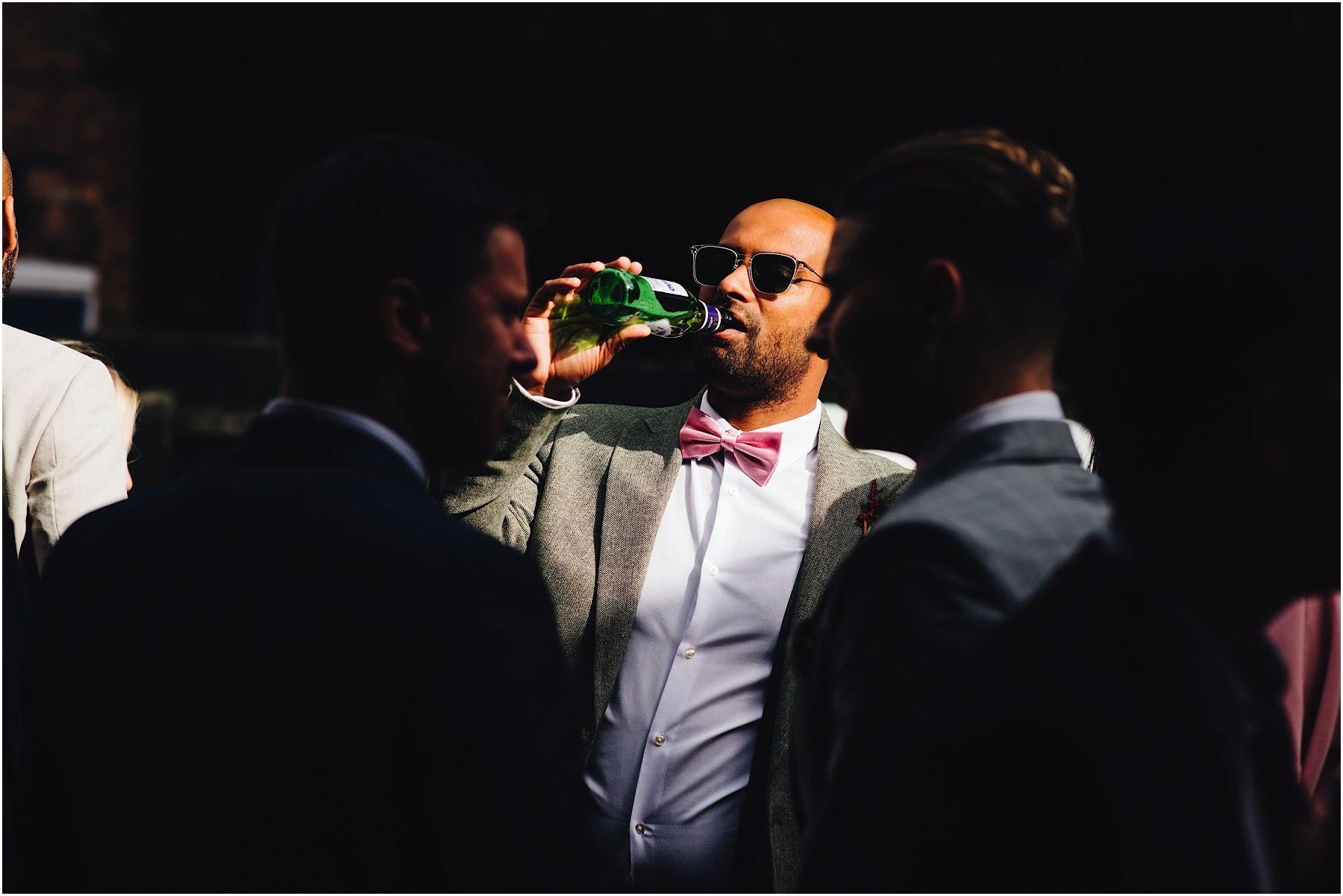 groomsmen having a drink at wedding