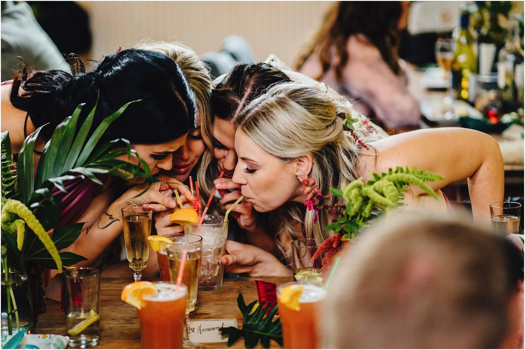 bride and bridesmaids sharing a cocktail
