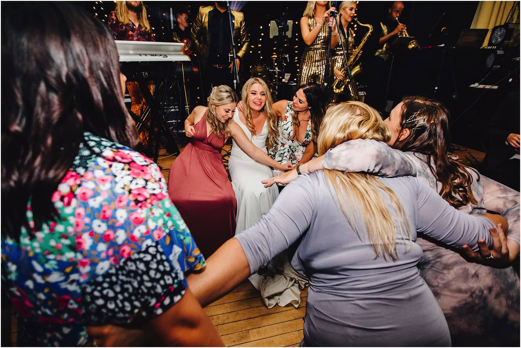 bride and guests sitting on dance floor