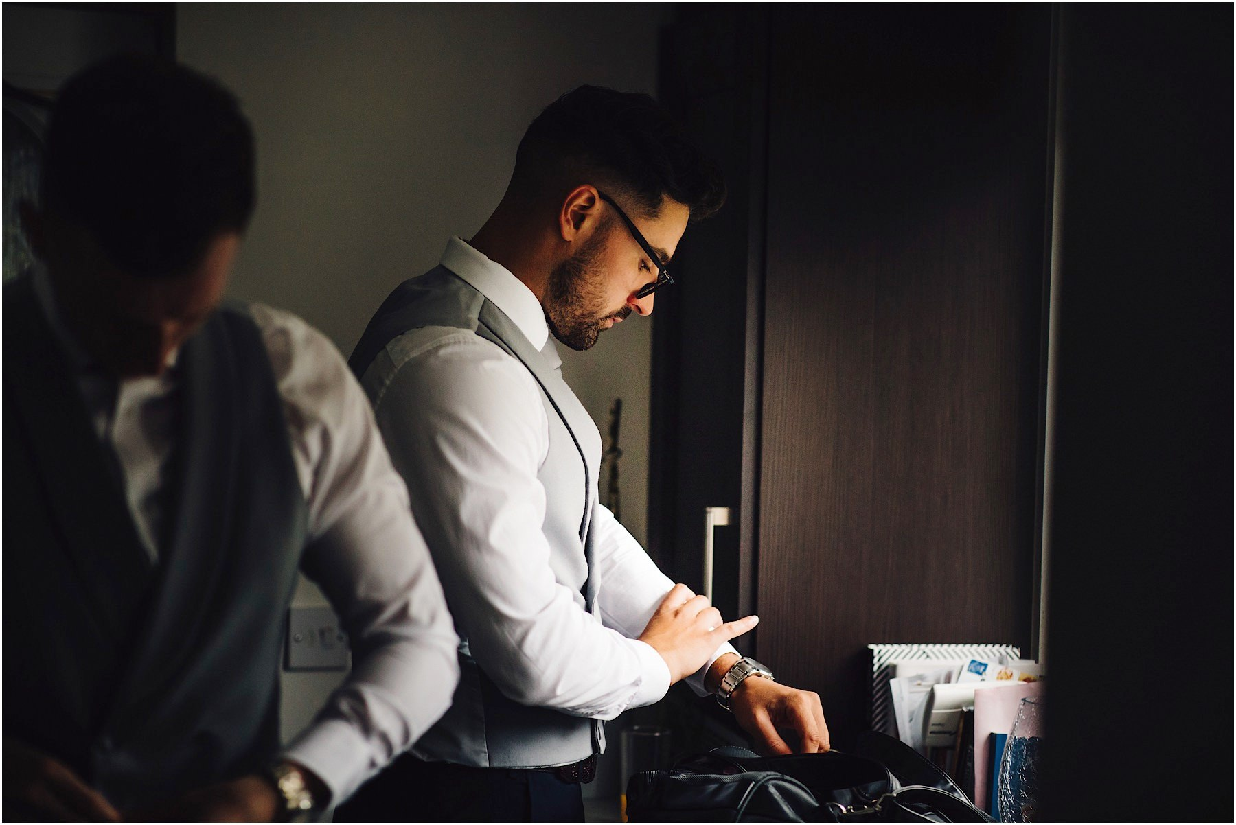 groomsman putting on cufflinks