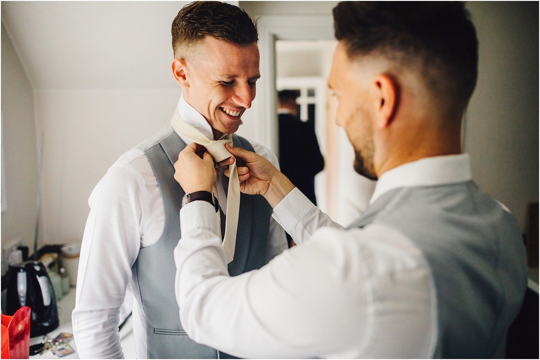 best man helping groom get dressed