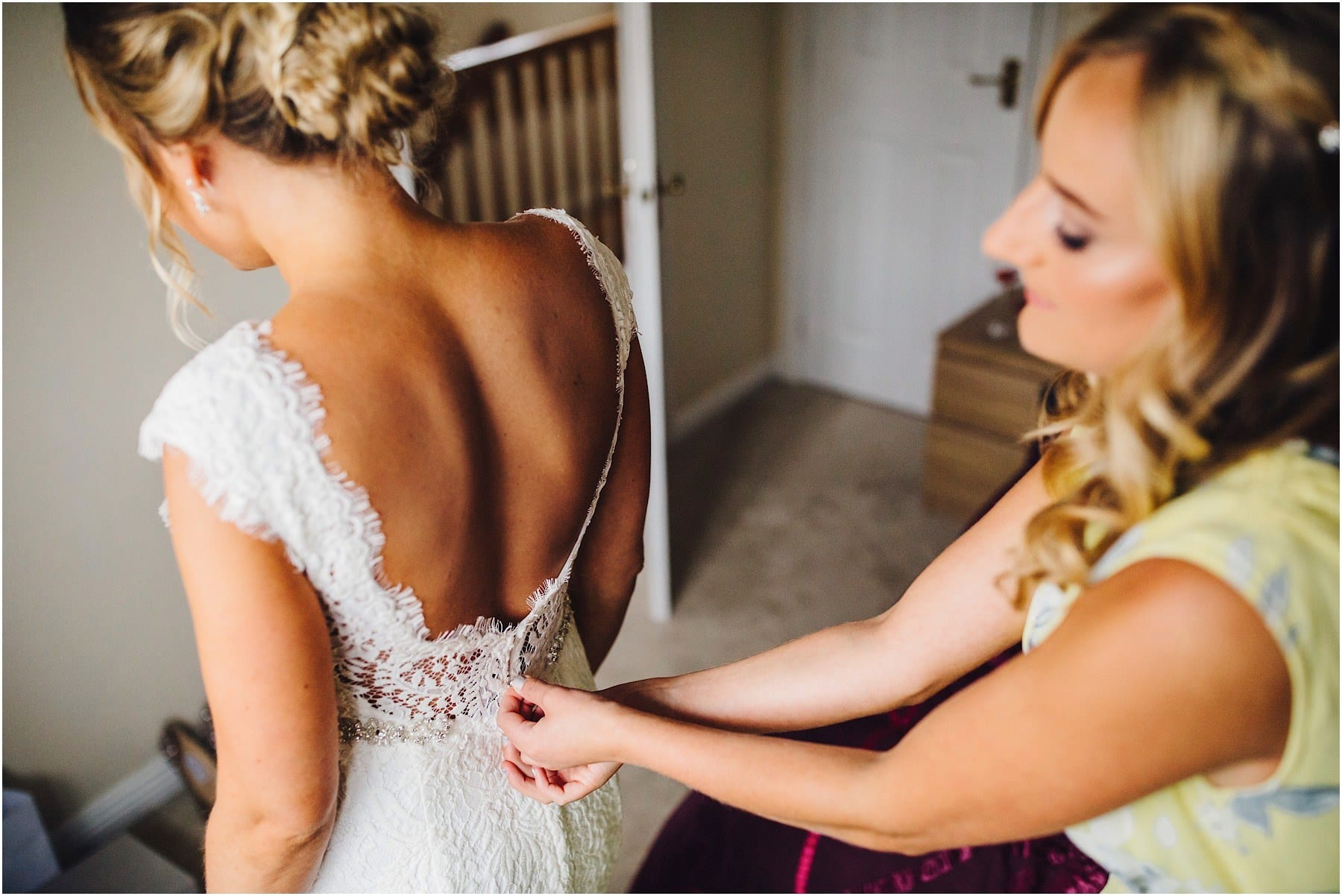 brides dress being zipped up
