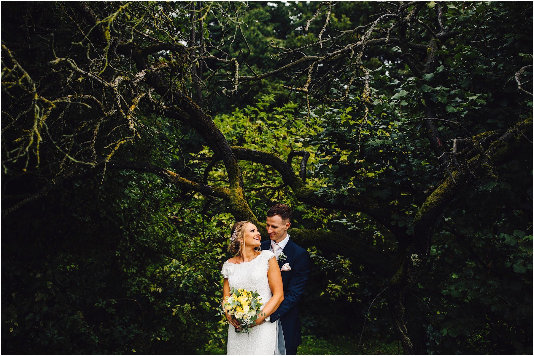 bride and groom pose under a tree