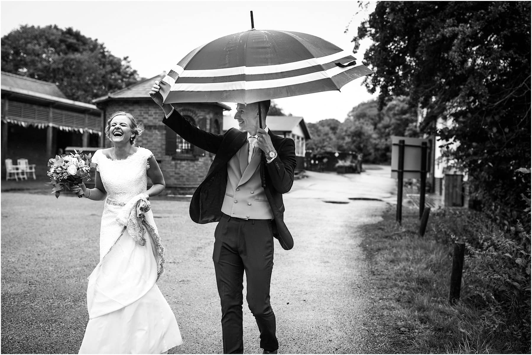bride and groom laughing in the rain
