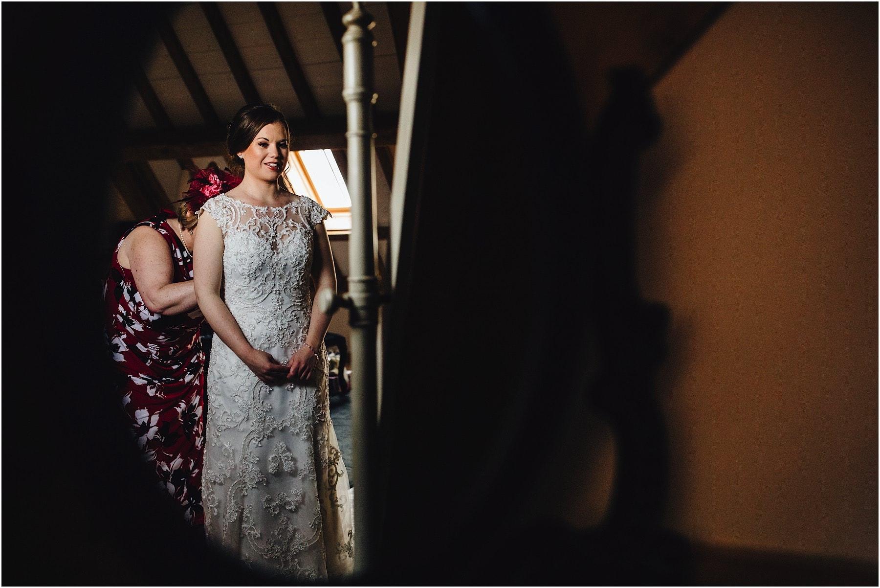 mother zipping up daughters wedding dress